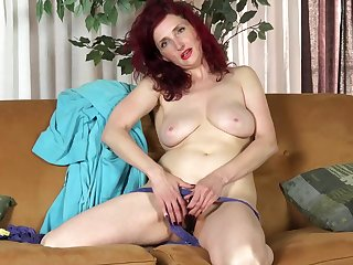 Red haired housewife, Zinnia Blue is using a ebony dildo dimension masturbating on the sofa